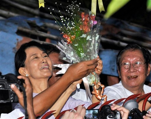 Myanmar's pro-democracy leader Aung San Suu Kyi, left, smiles after she received flowers from her supporters as she stands at the gate of her home Saturday, Nov. 13, 2010 in Yangon, Myanmar.