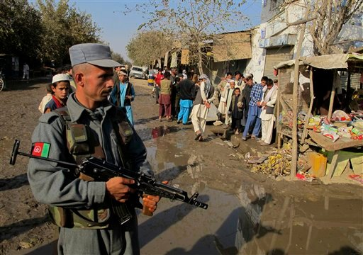 An Afghan police officer stands guard near the site of an explosion in Kunduz, Afghanistan, Saturday, Nov. 13, 2010. (AP Photo/Foulad Hamdard)