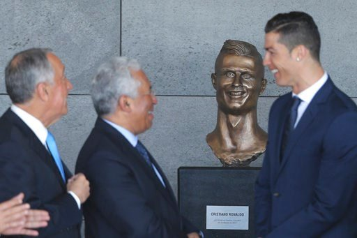 Portuguese president Marcelo Rebelo de Sousa, left, Portuguese Prime Minister Antonio Costa, 2nd left and Real Madrid's Cristiano Ronaldo stand next to a bust of the player at the Madeira international airport.