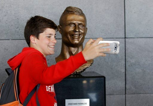 A boy takes a selfie next to the bust of Cristiano Ronaldo at the Madeira international airport.