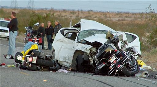 In this photo taken from video made Saturday, Nov. 13, 2010, rescuers and victims are seen at the site of a collision involving a car and several motorcycles on a remote desert highway near Ocotillo, Calif.