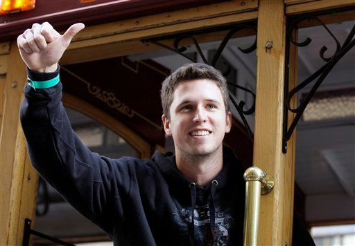 San Francisco Giants catcher Buster Posey celebrates while riding in a cable car during a baseball World Series parade in downtown San Francisco, Wednesday, Nov. 3, 2010. (AP Photo/Jeff Chiu)