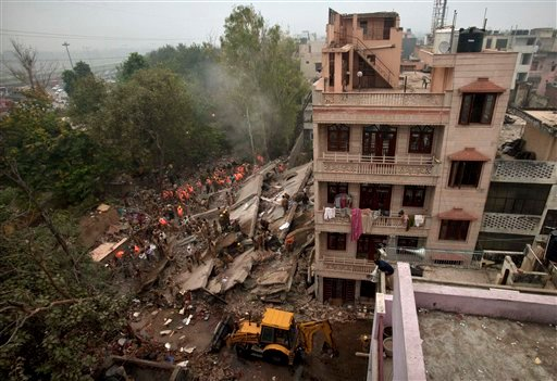 Rescue workers search amid debris after a four-story apartment building collapsed in New Delhi, India, Tuesday, Nov.16, 2010. Dozens of residents were killed and scores injured when the building collapsed late Monday night, police reports said. (AP Photo)