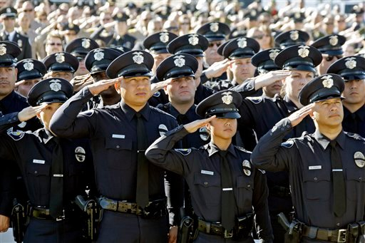 Hundreds of officers from many jurisdictions salute as they watch the funeral of Riverside Police Officer Ryan Bonaminio, broadcast on a giant screen to the overflow crowd of mourners outside, at Grove Community Church in Riverside, Calif.