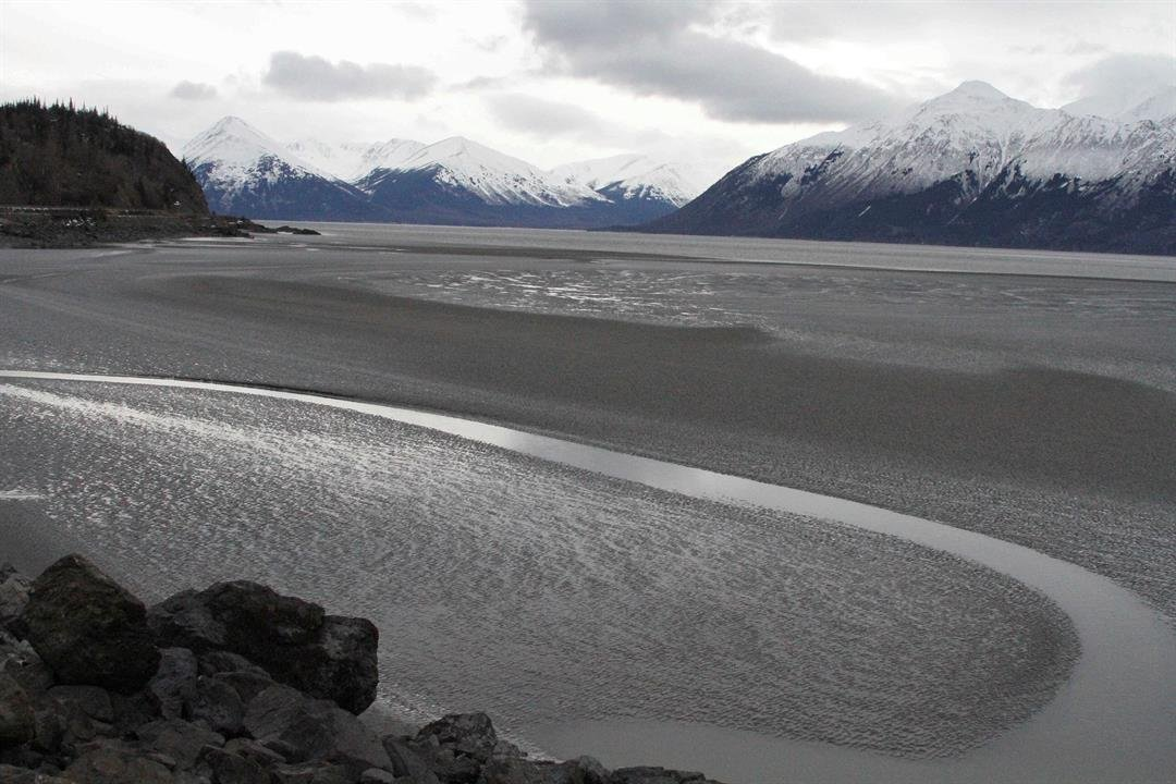 FILE - In this March 7, 2016, file photo, a ribbon of water cuts through the mud flats of Cook Inlet, just off the shore of Anchorage, Alaska. A pipeline spewing natural gas into Alaska's Cook Inlet may have started leaking in December, according to a fed