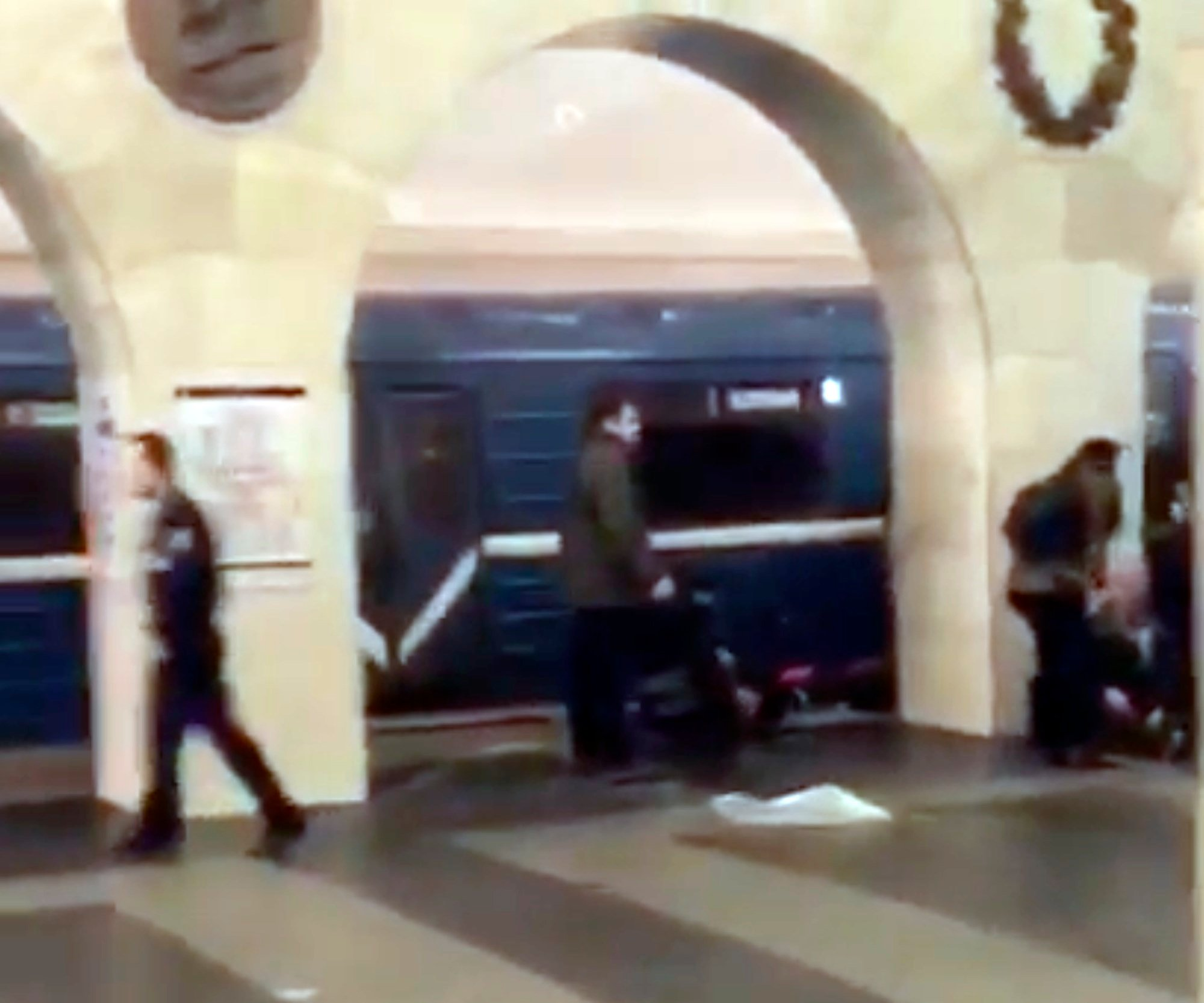 In this grab taken from AP video, Russian police officer, left, and people walk past the damaged train at the Tekhnologichesky Institut subway station in St.Petersburg, Russia, Monday, April 3, 2017. (AP video via AP)