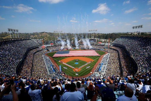 A giant American flag is unfurled on the field during the national anthem before the start of an opening day baseball game between the Los Angeles Dodgers and the San Diego Padres, Monday, April 3, 2017, in Los Angeles.