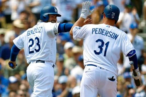 Los Angeles Dodgers first baseman Adrian Gonzalez, left, high-fives center fielder Joc Pederson, right, after scoring a run on a sacrifice fly ball by Pederson.