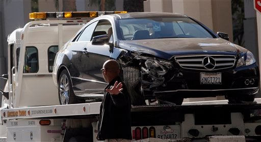 A tow truck driver stands beside a damaged Mercedes E350 in which a woman, well-known Hollywood publicist Ronni Chasen, 64, was shot several times in the chest and killed on Tuesday, Nov 16, 2010 in Beverly Hills, Calif.