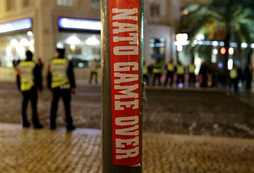 A sticker placed by an anti-NATO demonstrator is seen as Portuguese police officers stand guard following what the demonstrators called a flashmob for peace, outside the Rossio train station, in Lisbon, Portugal, Thursday, Nov. 18, 2010. (AP Photo/Lefteri