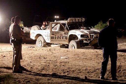 In this Aug. 14, 2010 file photo, law enforcement officers examine the accident scene where an off-road race truck, background, went out of control and plowed into a crowd of spectators during a race in Lucerne Valley, Calif.