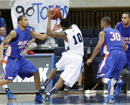 San Diego's Jordan Mackie attempts to split the Boise State defense of Robert Jordan, left, and Westly Perryman during the first half of a NCAA college basketball game Friday, Nov. 19, 2010, in San Diego. (AP Photo/Lenny Ignelzi)