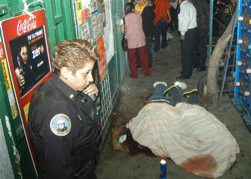 A police officer stands next to the bodies of two young men who were shot dead in the Tepito neighborhood in Mexico City early Thursday Oct. 28, 2010. (AP)