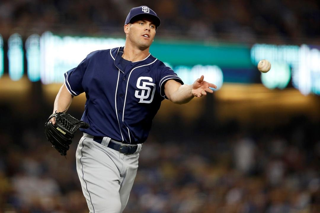 San Diego Padres pitcher Clayton Richard tosses the ball to first base to get Los Angeles Dodgers' Yasmani Grandal out during the fifth inning of a baseball game, Tuesday, April 4, 2017, in Los Angeles. (AP Photo/Ryan Kang)