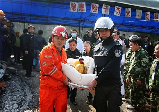 Rescuers and police officers carries a trapped miner on a stretcher out from the flooded Batian Coal Mine in Xiaohe town of Weiyuan county in southwest China's Sichuan province Monday, Nov. 22, 2010.