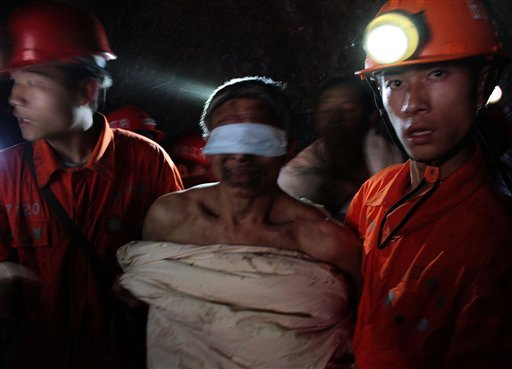 Rescuers escort a trapped miner wrapped in white quilt on their way out from the flooded Batian Coal Mine in Xiaohe town of Weiyuan county in southwest China's Sichuan province.