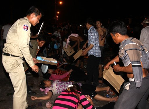 A Cambodian police officer helps injured Cambodians after a stampede onto a bridge at an accident site during the last day of celebrations of the water festival in Phnom Penh, Cambodia, Nov. 22, 2010. (AP Photo/Heng Sinith)