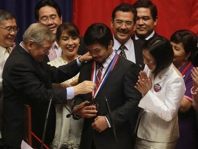 Filipino boxing champion and Congressman Manny Pacquiao, center, is bestowed the Congressional Medal of Distinction by Philippine House Speaker Feliciano Belmonte during a ceremony at the Lower House at Manila's Quezon city on Monday Nov. 22, 2010.