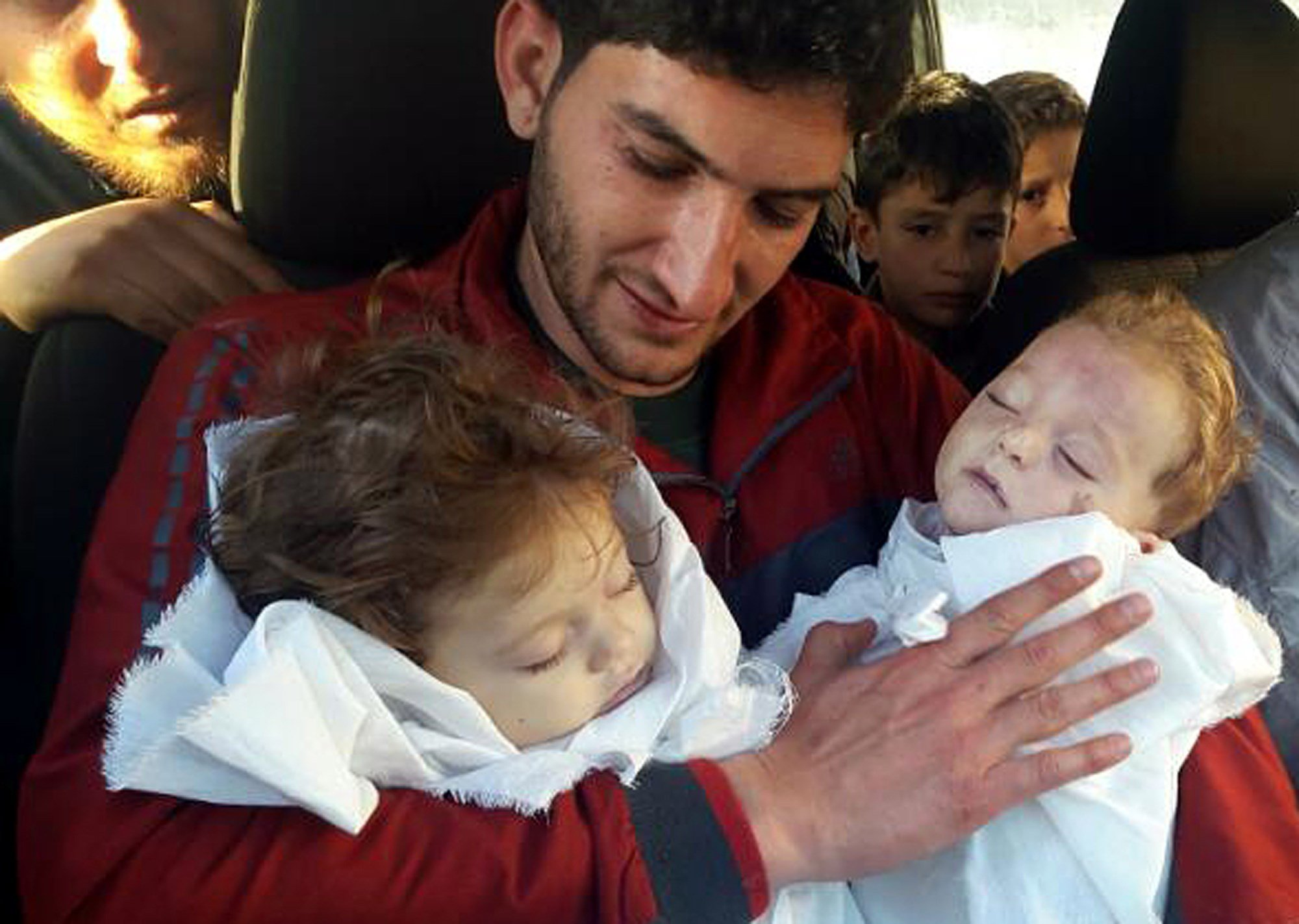 In this picture taken on Tuesday April 4, 2017, SAbdul-Hamid Alyousef, 29, holds his twin babies who were killed during a suspected chemical weapons attack, in Khan Sheikhoun in the northern province of Idlib, Syria.