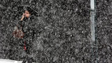 An unidentified woman stands at a bus stop along South 9th Street in downtown Tacoma, Wash., as snow falls Monday morning, Nov. 22, 2010. (AP Photo/The News Tribune, Janet Jensen)