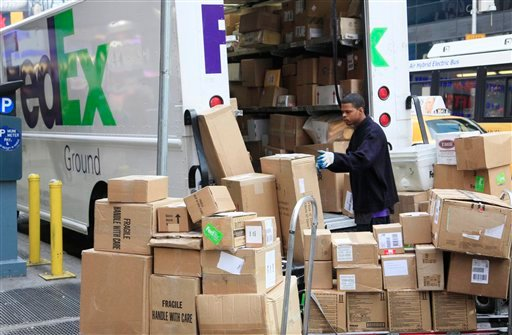 A FedEx employee sorts packages next to his truck, Tuesday, Nov. 23, 2010 in New York. The holiday season is the busiest of the year for the Memphis-based delivery company. (AP Photo/Mark Lennihan)