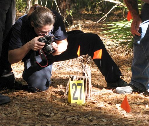 Diane Robinson of the American Humane Association marks and photographs details of a staged crime scene during a veterinary forensics seminar at the University of Florida in Gainesville, Fla.