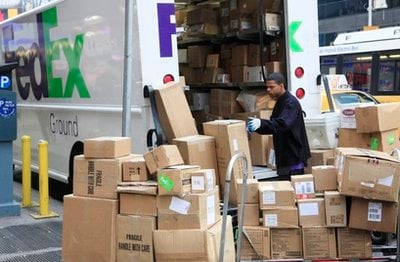 A FedEx employee sorts packages next to his truck, Tuesday, Nov. 23, 2010 in New York. The holiday season is the busiest of the year for the Memphis-based delivery company.