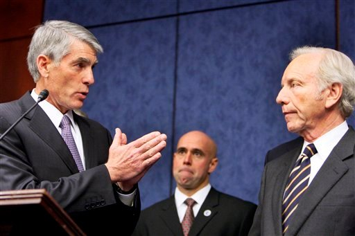 Sen. Mark Udall, D-Colo., left, gestures to Sen. Joseph Lieberman, I-Conn., during a news conference on Capitol Hill in Washington, Thursday, Nov. 18 ,2010, to push for the repeal of the military Don't Ask Don't Tell rule. (AP Photo/Ann Heisenfelt)