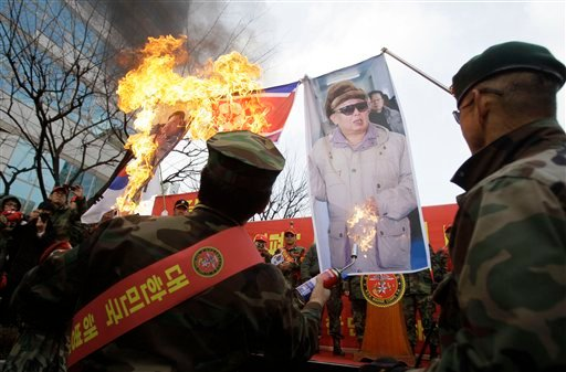 Former South Korean marines burn images of North Korean leader Kim Jong il, right, and his son Kim Jong Un, during a rally denouncing North Korea, Saturday, Nov. 27, 2010, in Seoul, South Korea. (AP Photo/Wally Santana)