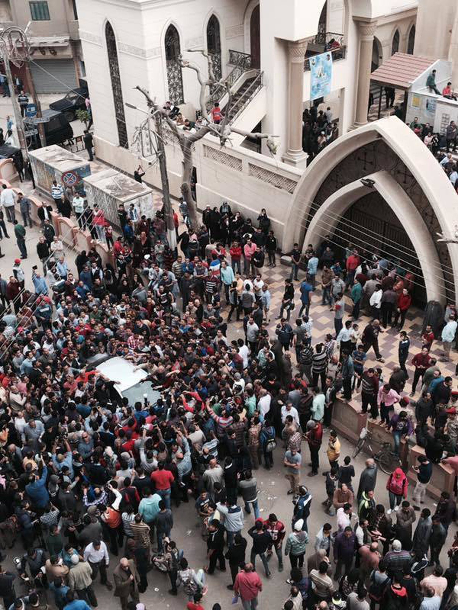 Relatives and onlookers swarm around a car outside a church after a bomb attack in the Nile Delta town of Tanta, Egypt, Sunday, April 9, 2017. (AP Photo/Nariman El-Mofty)