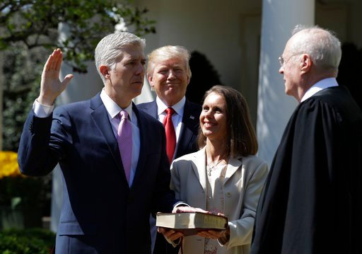 President Donald Trump watches as Supreme Court Justice Anthony Kennedy administers the judicial oath to Judge Neil Gorsuch during a re-enactment in the Rose Garden of the White House White House in Washington April 10, 2017. (AP Photo/Evan Vucci)