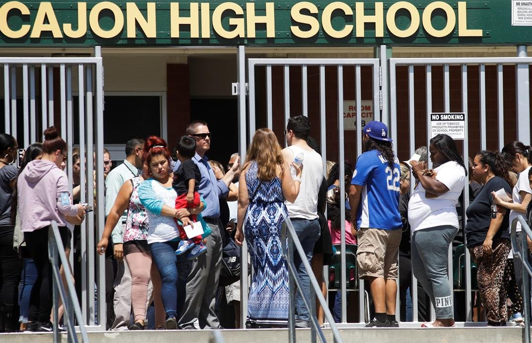 Parents and guardians of North Park Elementary School students wait at Cajon High School to pick up their children Monday, April 10, 2017, in San Bernardino, Calif. (AP Photo/Jae C. Hong)
