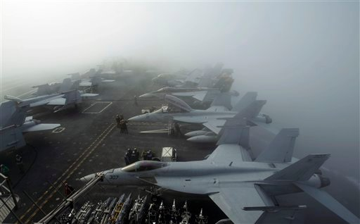 U.S. Navy F/A-18F Super Hornet fighter attack aircrafts sit in heavy fog on the deck of the USS George Washington. (AP Photo/Wally Santana)
