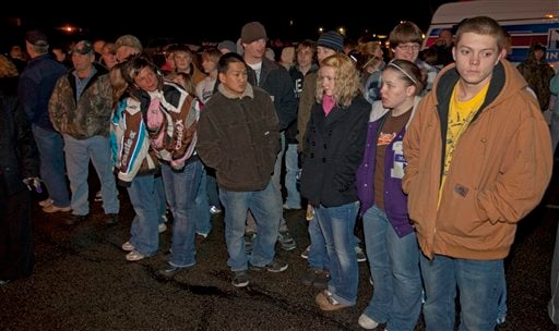 Students and parents wait in a parking lot near Marinette High School as they await word on a hostage situation at the school Monday night Nov. 29, 2010 in Marinette, Wis.