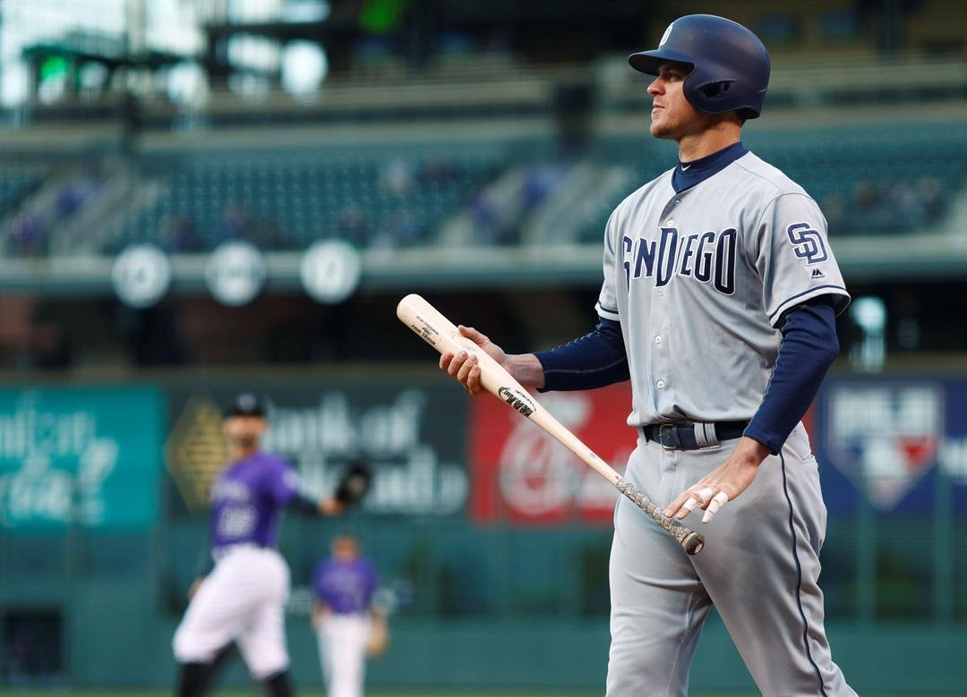 San Diego Padres' Wil Myers, front, reacts after swinging and missing a pitch thrown by Colorado Rockies starting pitcher Tyler Chatwood in the first inning of a baseball game, Monday, April 10, 2017, in Denver. (AP Photo/David Zalubowski)