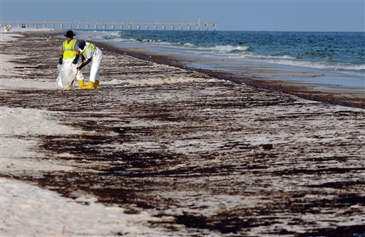 June 23, 2010 file photo: crews work to clean up oil from the Deepwater Horizon oil spill washed ashore at Pensacola Beach in Pensacola Fla. (AP Photo/ Michael Spooneybarger, File)