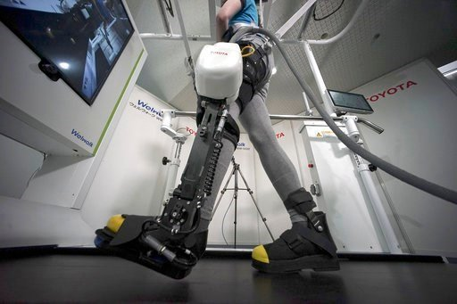 A model demonstrates the Welwalk WW-1000, a wearable robotic leg brace designed to help partially paralyzed people walk at the main system with treadmill and monitor, at Toyota Motor Corp.'s head office in Tokyo.
