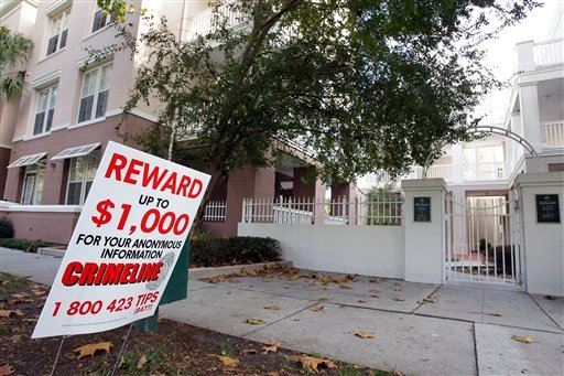 This photo taken Wednesday, Dec. 1, 2010, shows a reward sign near the entrance to a condominium in Celebration, Fla. Police are investigating the first ever murder in Celebration, the Disney-developed community in Florida. (AP Photo/John Raoux)