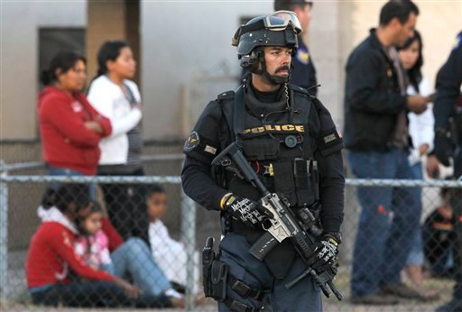 A member of the Phoenix Police Department S.W.A.T. team stands in front of a home where 10 juveniles were rescued at a suspected drop house Thursday, Dec. 2, 2010, in Phoenix.