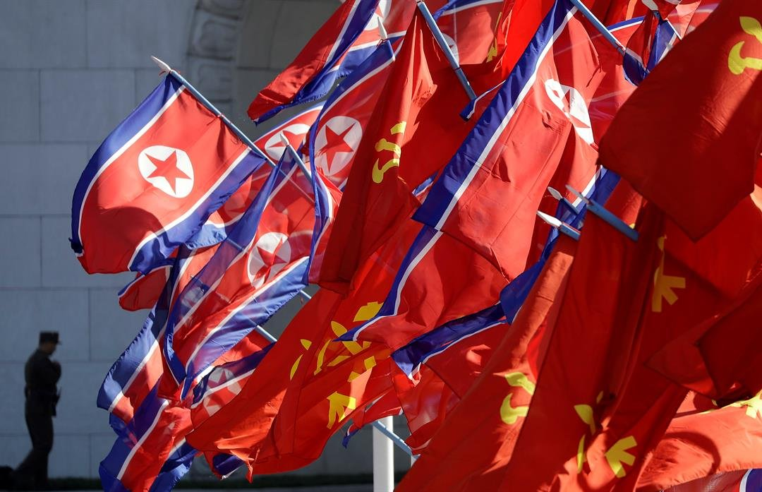 North Korean and Workers' Party flags flutter as a soldier guards the entrance to the newly completed Ryomyong residential area, a collection of more than a dozen apartment buildings, ahead of its official opening ceremony on Thursday, April 13, 2017, in