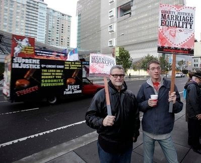 Gus Thompson, left, and Eric Hufford of San Diego, hold signs in support of gay marriage as a truck with an anti-gay marriage message drives past them before a hearing in the Ninth Circuit Court of Appeals, Monday, Dec. 6, 2010, in San Francisco.