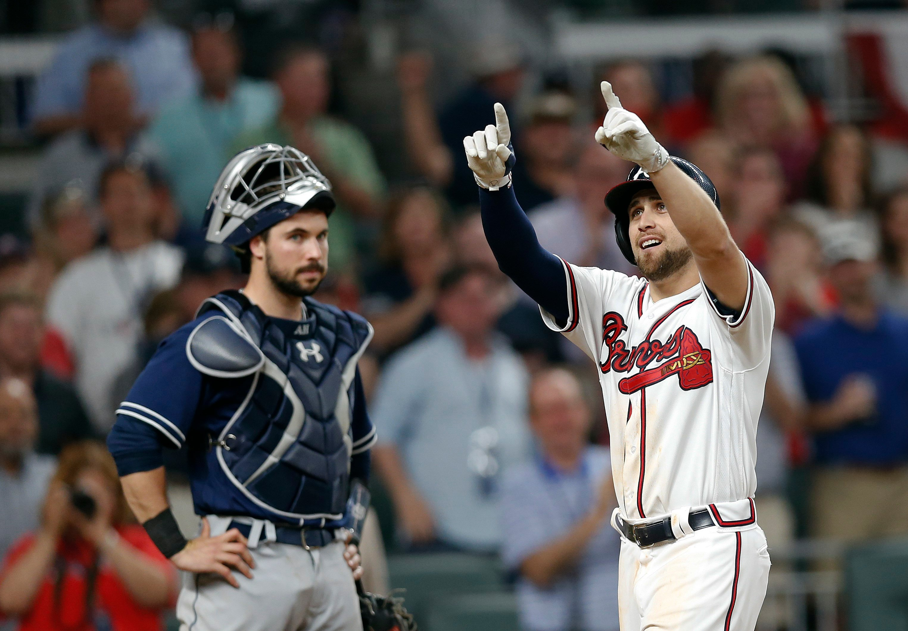 Atlanta Braves' Ender Inciarte, right, gestures as he crosses home plate in front of San Diego Padres catcher Austin Hedges, left, after hitting a two-run home run in the sixth inning of a baseball game Friday, April 14, 2017, in Atlanta. The home run was