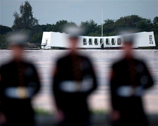 With the USS Arizona memorial in the background, U.S. Marines stand at attention, Tuesday, Dec. 7, 2010, in Pearl Harbor, Hawaii. Tuesday marks the 69th anniversary of the attack on Pearl Harbor. (AP Photo/Marco Garcia)