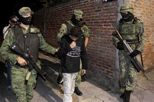 """Soldiers escort a 14-year-old known as """"El Ponchis"""" who is suspected of working as a killer for a drug cartel, in the city of Cuernavaca, Mexico, Friday Dec. 3, 2010."""