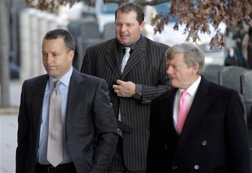 Former Major League Baseball pitcher Roger Clemens, center, accompanied by his lawyers, Michael Attanasio, left, and Rusty Hardin, arrives at court in Washington, Dec. 8, 2010. (AP Photo/Charles Dharapak)