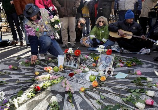 Gary Dos Santos, left, arranges flowers on the Imagine mosaic in the Strawberry Fields section of New York's Central Park, Wednesday, Dec. 8, 2010, the 30th anniversary of the death of John Lennon. (AP Photo/Richard Drew)