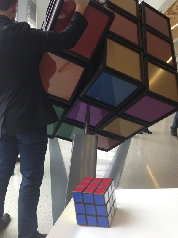 A traditional Rubik's Cube sits on a podium in the foreground while a person operates an oversized version shortly after its unveiling inside the University of Michigan's G.G.