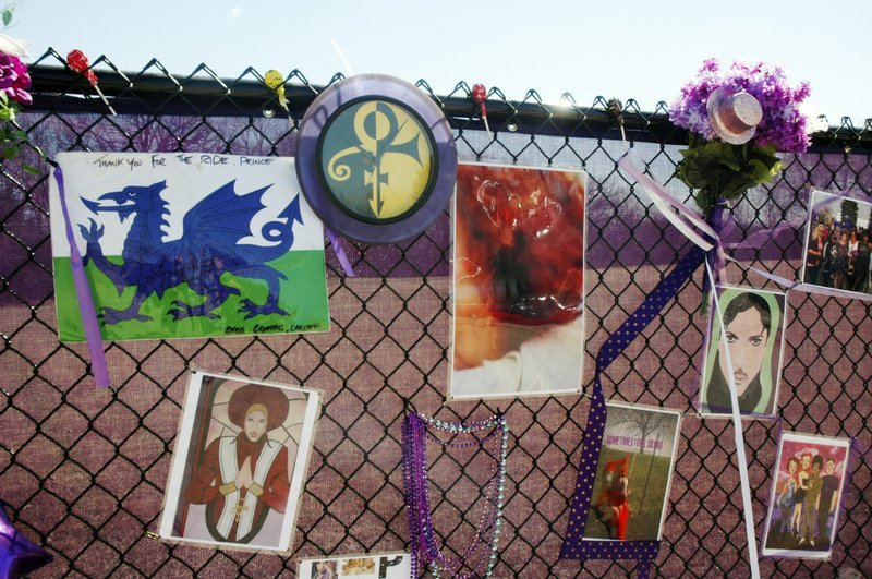 In this April 6, 2017, photo, fan artwork of Prince hangs on a new memorial fence in the parking lot of Paisley Park Museum, the former home and recording complex of the late superstar in Chanhassen, Minn.