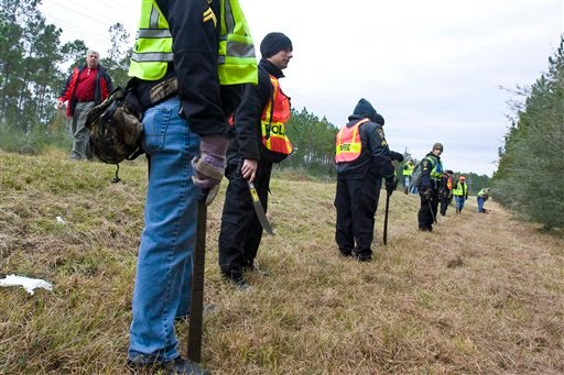 Investigators work a crime scene along Miss. 57, several miles north of Vancleave, Miss., where a body was discovered on Wednesday, Dec. 8, 2010.
