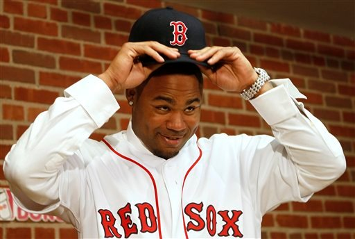 Carl Crawford tries on his new hat during a news conference announcing his signing by the Boston Red Sox baseball club at Fenway Park in Boston Saturday, Dec. 11, 2010. (AP Photo/Winslow Townson)